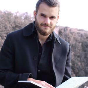 Profilbild von Autor Jan Baßler welcher ein Buch in der Hand hält und in die Kamera schaut