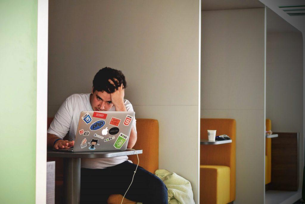 Self-Publishing Fehler Beispielbild:  Frustriert schauender Mann sitzt an einem Tisch