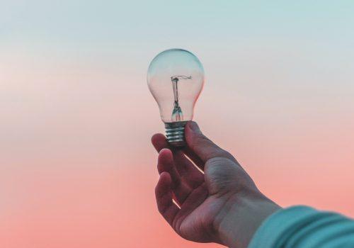 Eine Hand hält eine Glühbirne vor einen Sonnenuntergang als Zeichen für eine Idee