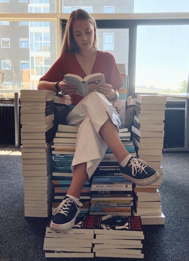 Eine junge Frau hat ihr eigenes Buch veröffentlicht und sitz auf einem aus Büchern gebauten Sitz