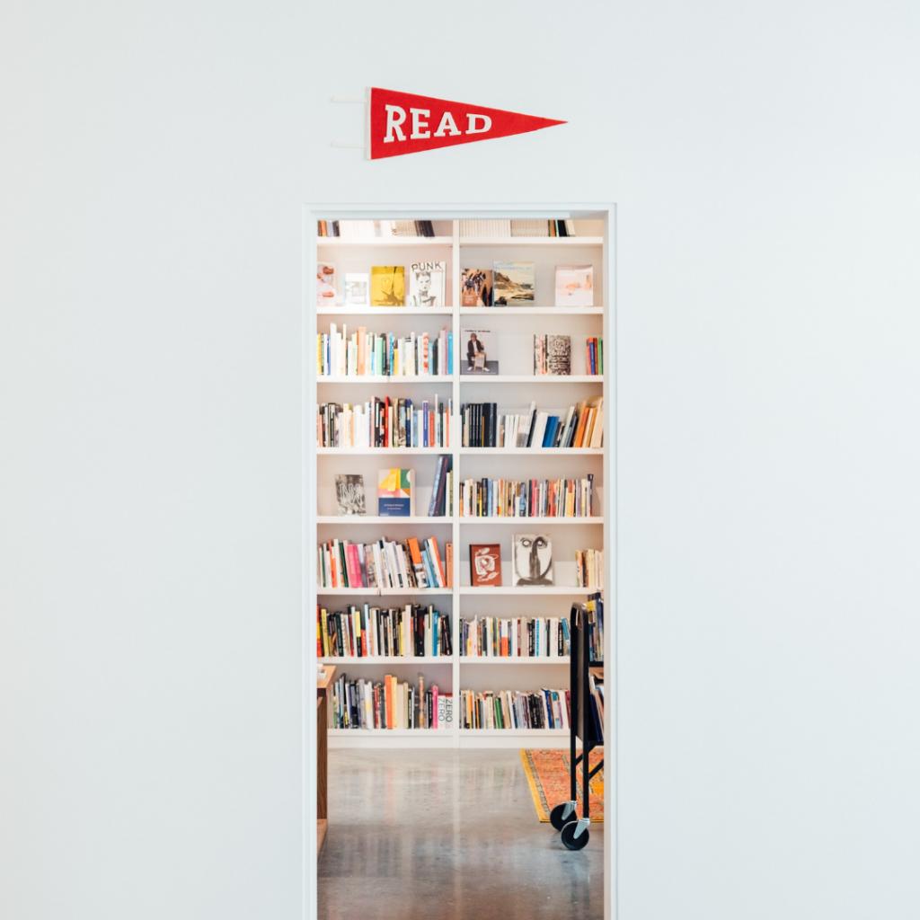 """Offener Eingang zu einem Raum voller Bücherregale. Über dem Eingang steht ein roter Pfeil mit der Aufstrift """"Read"""""""